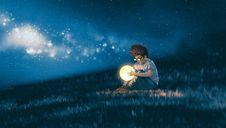 Un garçon concentré sur une boule lumineuse qu'il tient dans les mains