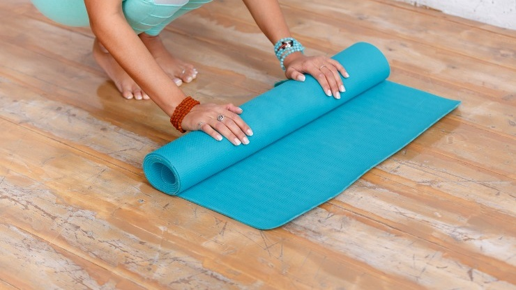 Data 2fimages 2fzrhukfhtbmoqpiydhpul closeup of attractive young woman folding blue yoga or fitness mat picture id942285912